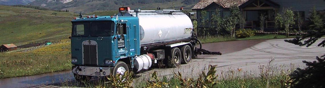 Tanker truck applying Coherex dust suppressant and soil stabilizer