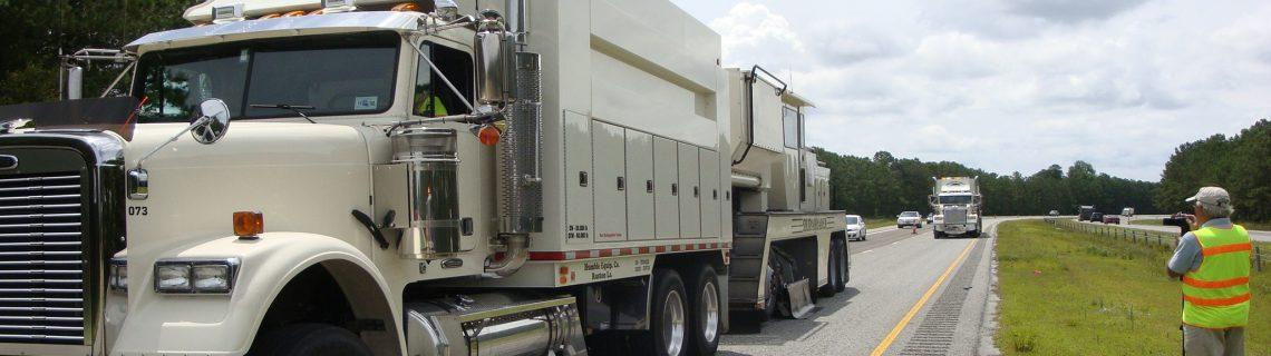 Skidabrader trucks performing road surface texturing on four-lane highway