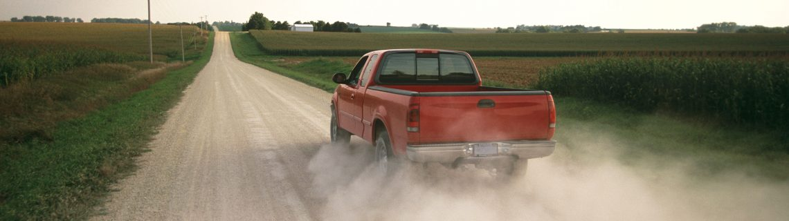 A red pickup truck driving down a dusty country road