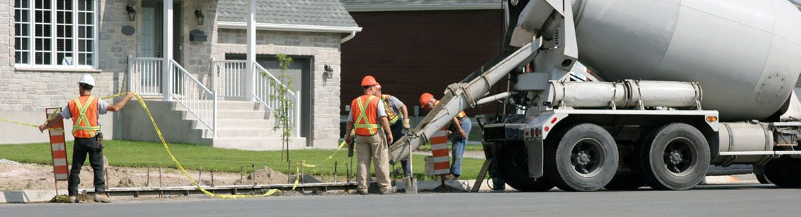 Road construction crew pouring concrete from a concrete mixer truck in a residential neighborhood