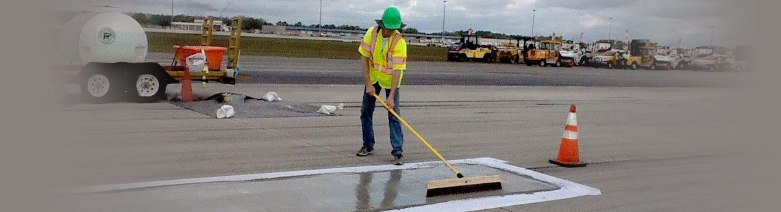 Pavement Technology Inc employee applying SurfCrete to a concrete airport runway.