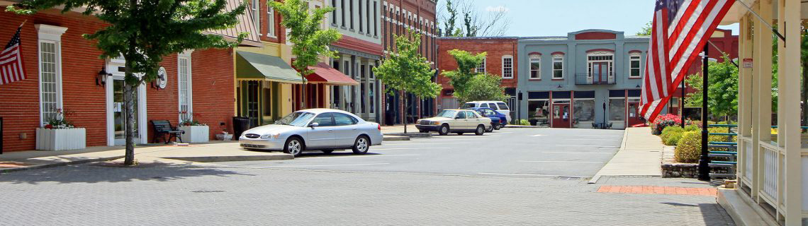 Paved street in a small town with storefronts, parked cars and US flags